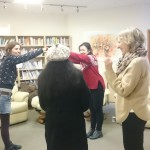 four women standing in a room with books holding their arms to form an arch