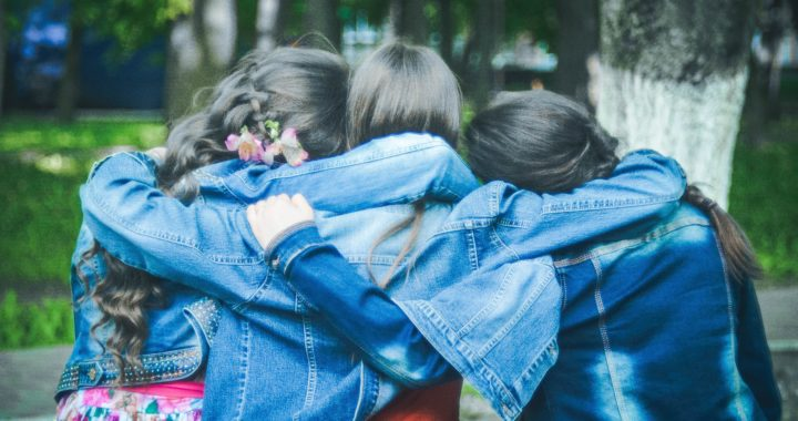 three girl friends wearing denim jackets facing away with their arms around each other as they look towards trees