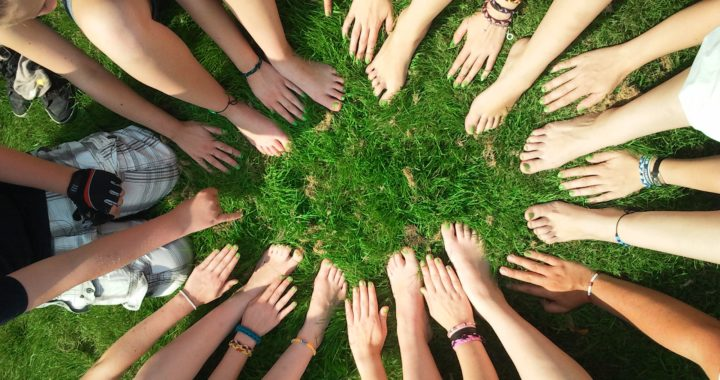 a group of people sitting outside on the grass with their feet and hands in a circle
