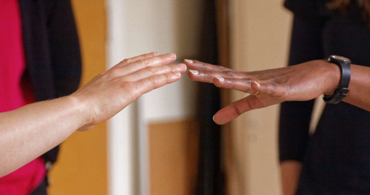 two people from different races reaching their hands out to one another with their finger tips almost touching