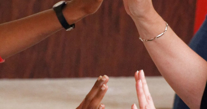 two sets of hands of people from different races reaching and mirroring each other