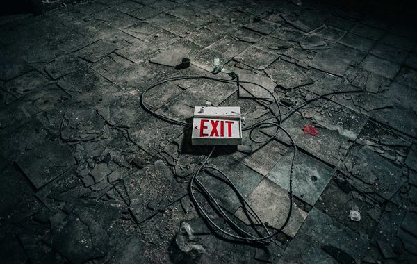 a broken tiled surface with a broken exit sign laying on the ground with the wires loose around it