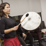 A woman standing banging a drum