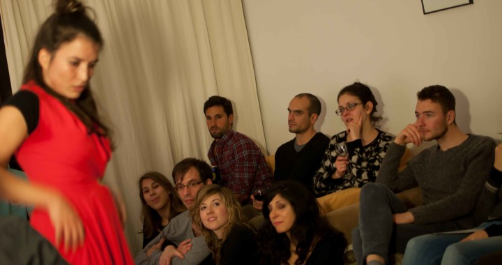 A group of people in a living room watching a woman perform