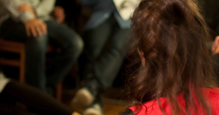 a woman in a red dress sitting down talking to a room of people