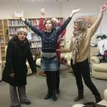 four women raising their arms in the air