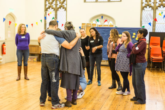 a group of people hugging in the church whilst people watch