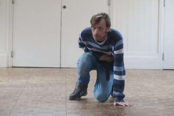 a man in blue crouched down in pain