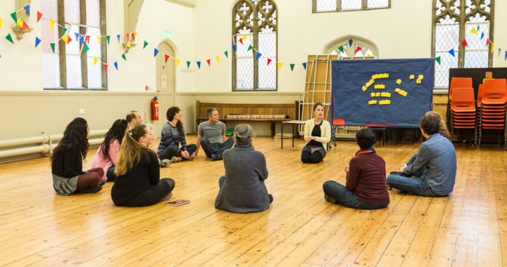a group of people sit in a circle on a wooden floor in a church