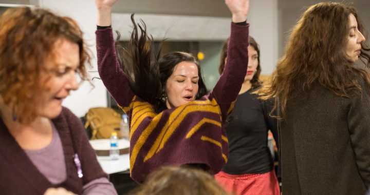 in a crowded room a woman in a purple and yellow jumper is reaching up into the air